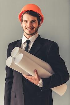 スーツと保護用のヘルメットでハンサムな若い建築家。