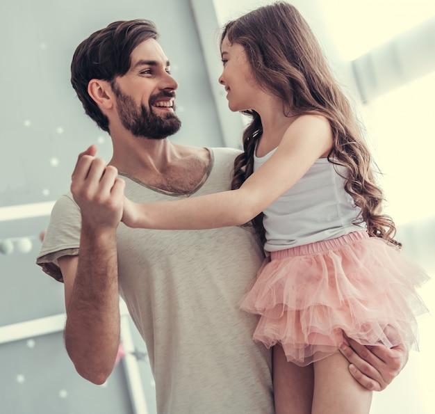 娘と彼女のハンサムな若いお父さんが踊っています。