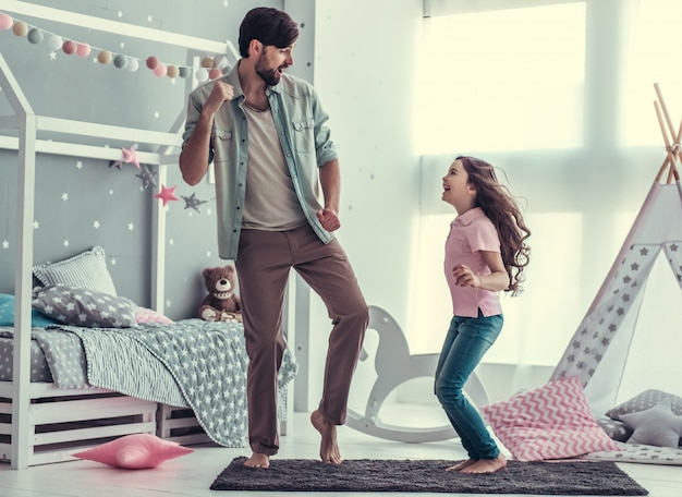 Дочь и ее красивый папа танцуют и улыбаются.