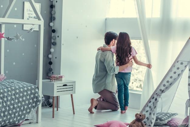 小さな娘と彼女のお父さんは窓の外を見ています。