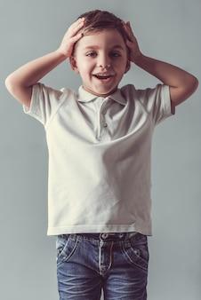 かわいい男の子はカメラを見て、頭の上に手を維持しています。