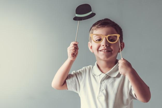 かわいい男の子は紙の帽子と眼鏡を持っています。