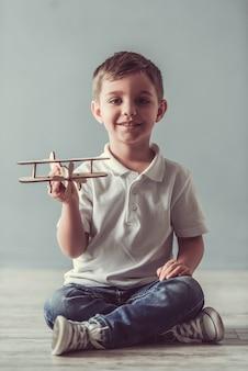 かわいい男の子はカメラ目線、おもちゃの飛行機で遊んでいます。