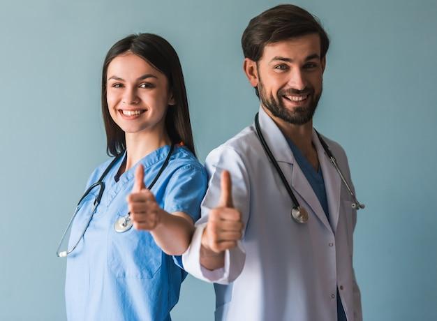 美しい若い医者は親指を見せています。