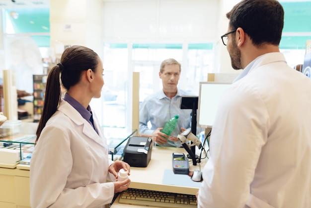 Фармацевты разговаривают с клиентом в аптеке.