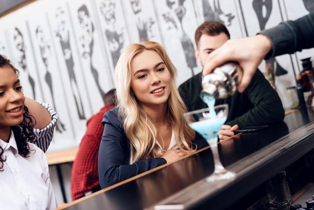 女の子はカクテルを注文し、バーカウンターに座ります。
