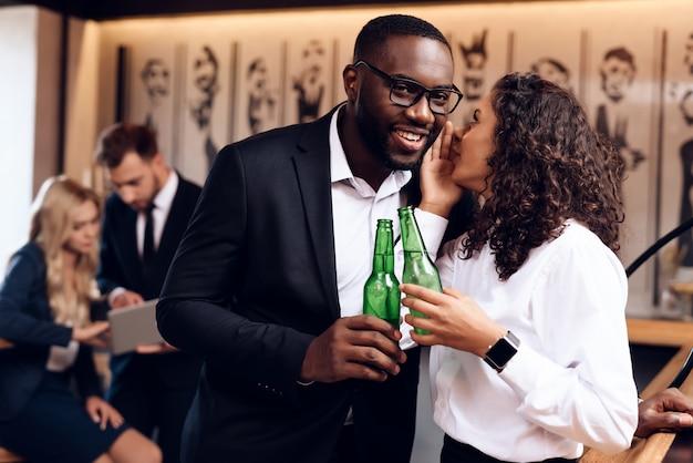 男と女がバーでアルコールを一緒に飲んでいます。