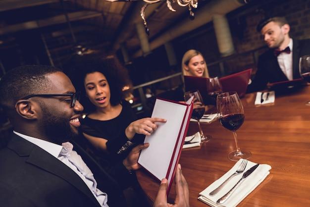 若い会社がレストランに一緒に座っています。
