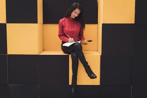 Девушка пишет в журнале для записей.