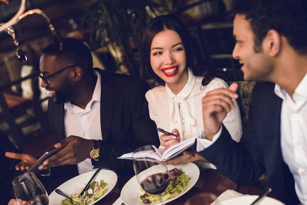 人々はレストランでアルコール飲料を飲んでいます。