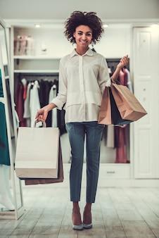 買い物袋を保持しているアフロアメリカンの女の子。