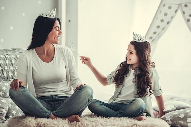 女の子と彼女のお母さんは王冠で遊んでいる間笑っています。