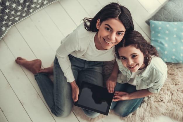 女子高生と彼女のお母さんがデジタルタブレットを使用しています。
