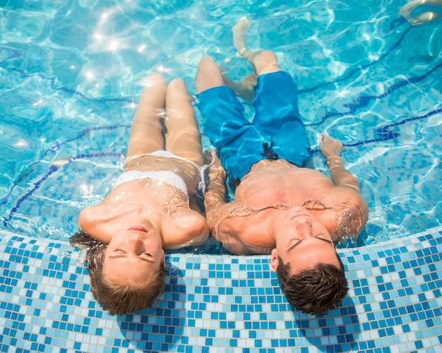 Взгляд сверху молодой пары отдыхает в бассейне.