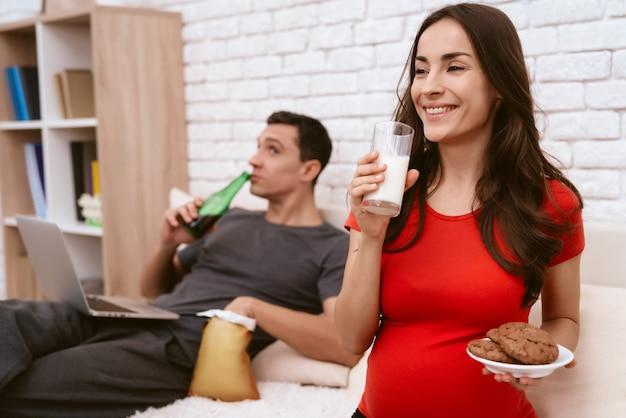 Беременная женщина пьет молоко и улыбается.