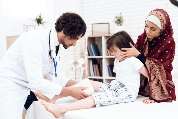 医者は小さな男の子に包帯で足を巻き戻します。