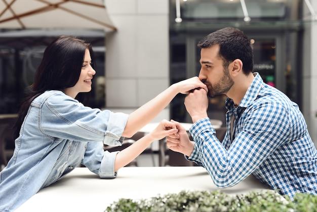 愛情のこもった少年は屋外カフェで少女の手にキスします。