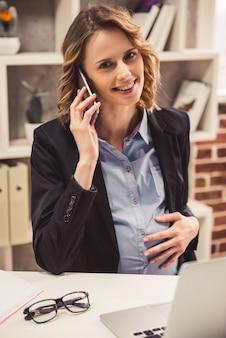 Деловая женщина в костюме разговаривает по мобильному телефону.