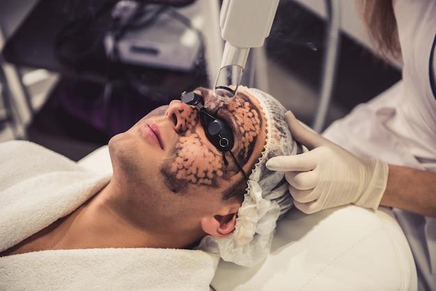 医者は彼の顔に黒いマスクを置きます。