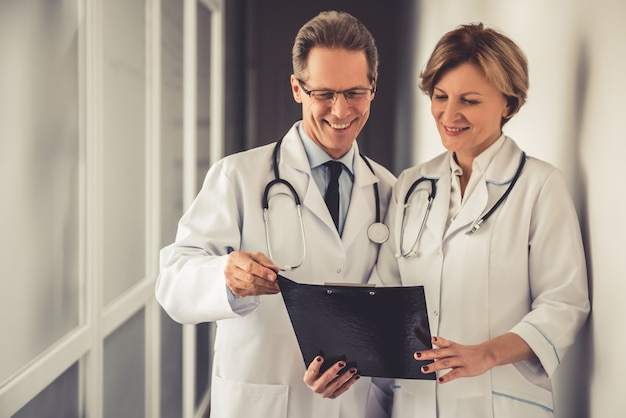 白衣の医師たちが文書を話し合っています。
