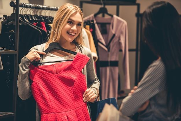 美しい女の子たちはドレスを選んで笑っています。