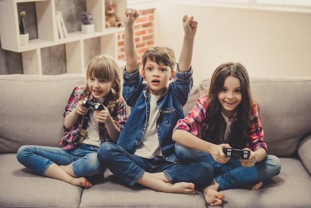 Веселые дети сидят вместе на диване у себя дома.