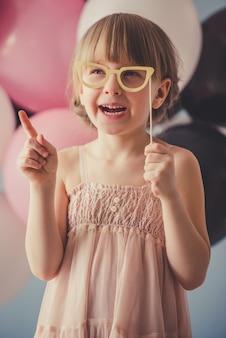 ドレスを着たかわいい王女は、紙の眼鏡でポーズをとっています。