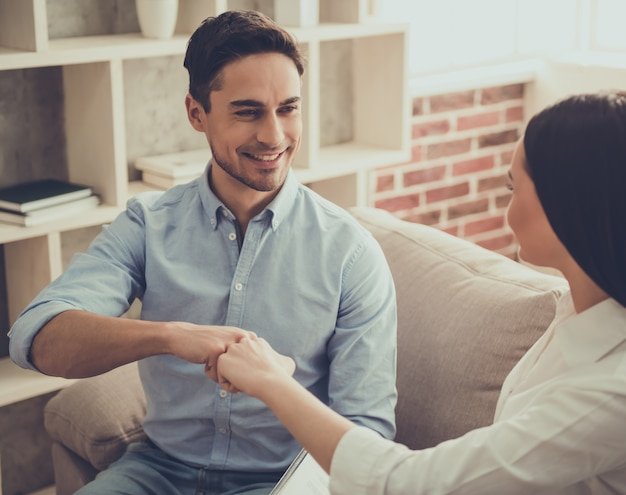 心理学者とハンサムなクライアントが拳に触れています。