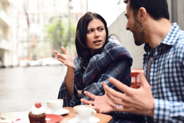 屋外カフェで口論している気違いの結婚パートナー。