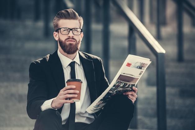 Бородатый бизнесмен в классическом костюме и очках.