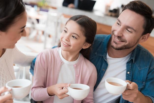 Счастливое семейное зимнее теплое время чая в уютном кафе.