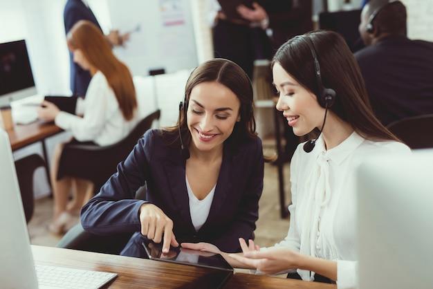Девушки-операторы колл-центра общаются друг с другом.