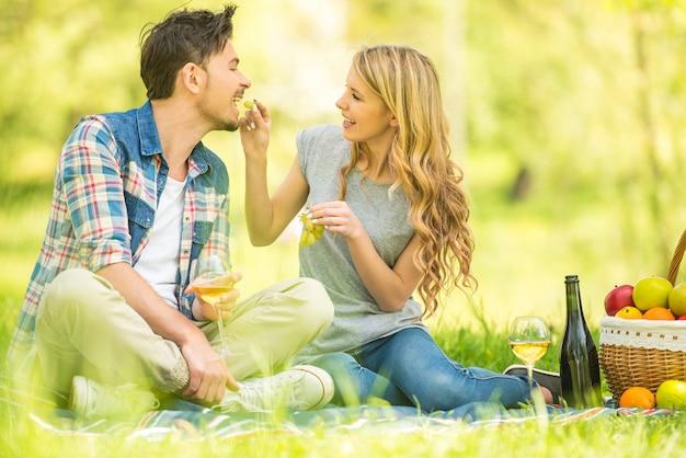 カップルはピクニックをして、ブドウを食べて、そしてワインを飲みます。