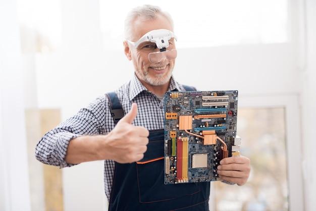 幸せな経験豊富なエンジニアがマザーボードを抱えています。