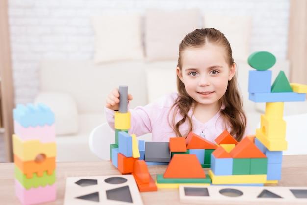 Маленькая девочка играет с красочными кубиками.