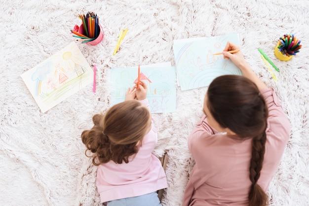 Мама и дочь вместе рисуют на бумаге карандашами.