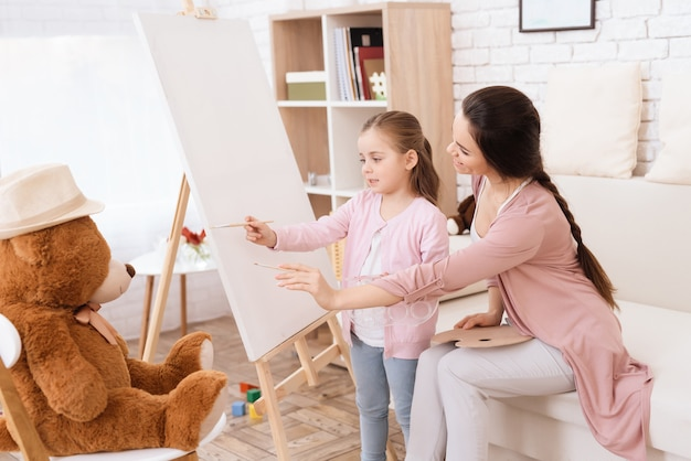 彼女の母親と一緒に小さな女の子が描きます。