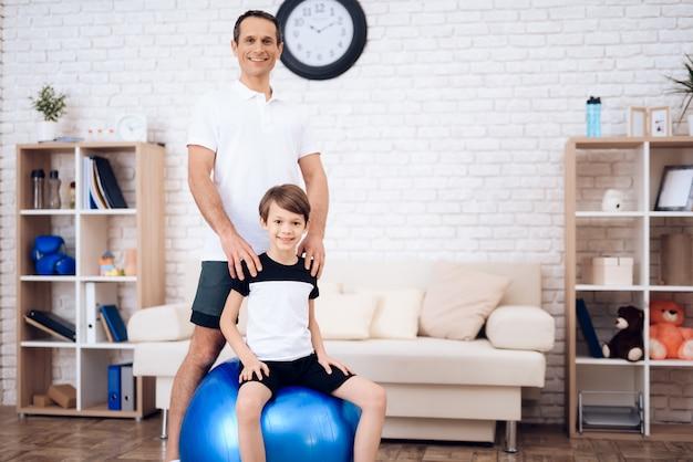 Отец и сын занимаются фитнесом вместе с фитболом.