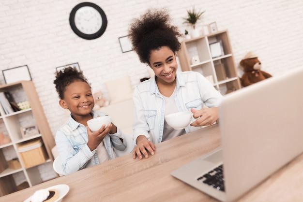 Мама и дочка мулата смотрят что-то на ноутбуке