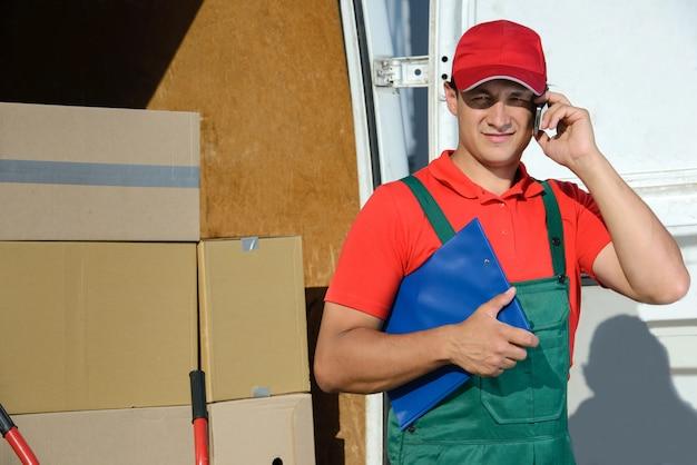 Мужской курьер почтовой доставки перед грузовым фургоном.
