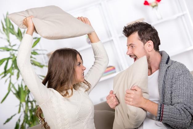 女の子と男の子が自宅で枕を破っています。