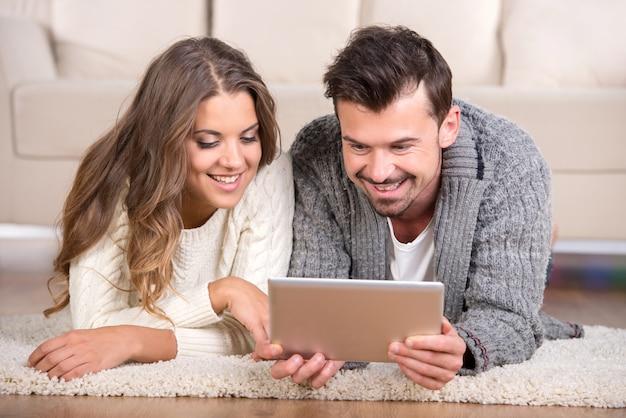幸せなカップルは床に横になっているとタブレットを見ています。