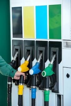 ガソリンスタンドで燃料ノズルを使って人間の手のクローズアップ。