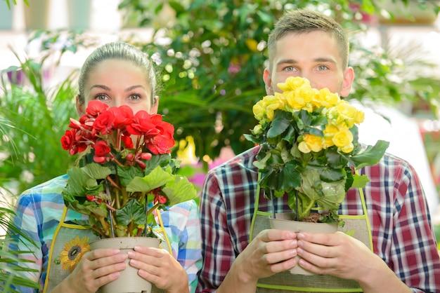 男と女は顔の近くに花を抱えてそれらを嗅ぐ。