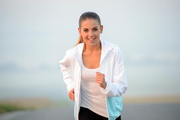 日当たりの良い夏に緑豊かな公園で走っている美しい女性。