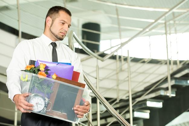 解雇された実業家は彼の袋を詰めて事務所を出発しました。