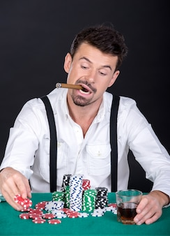Человек играет в покер с сигарой и стаканом виски.