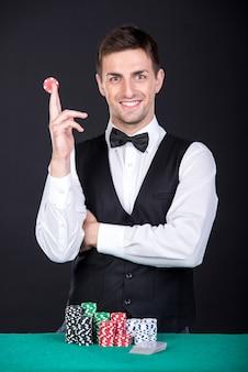 緑色のテーブル上のギャンブルのチップを持つ笑顔のディーラー。