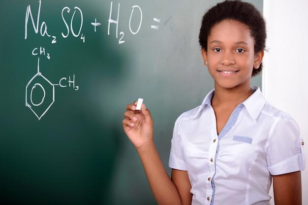 アフリカの学生が黒板に数学の問題をやっています。