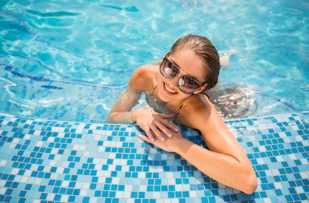 美しい女性はスイミングプールでリラックスしています。